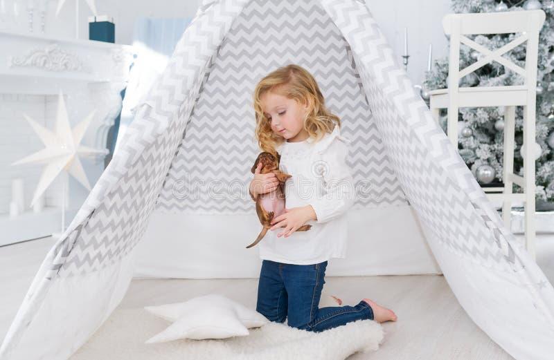 Lilla flickan spelar med den lilla valphunden nära vigvammet i jullekrum arkivfoto