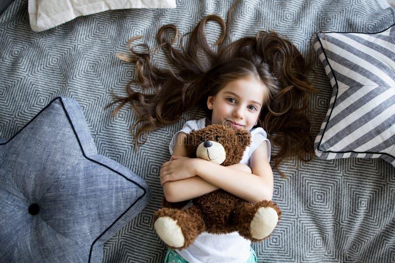 Lilla flickan spelar med en leksakbjörn på sängen royaltyfri bild