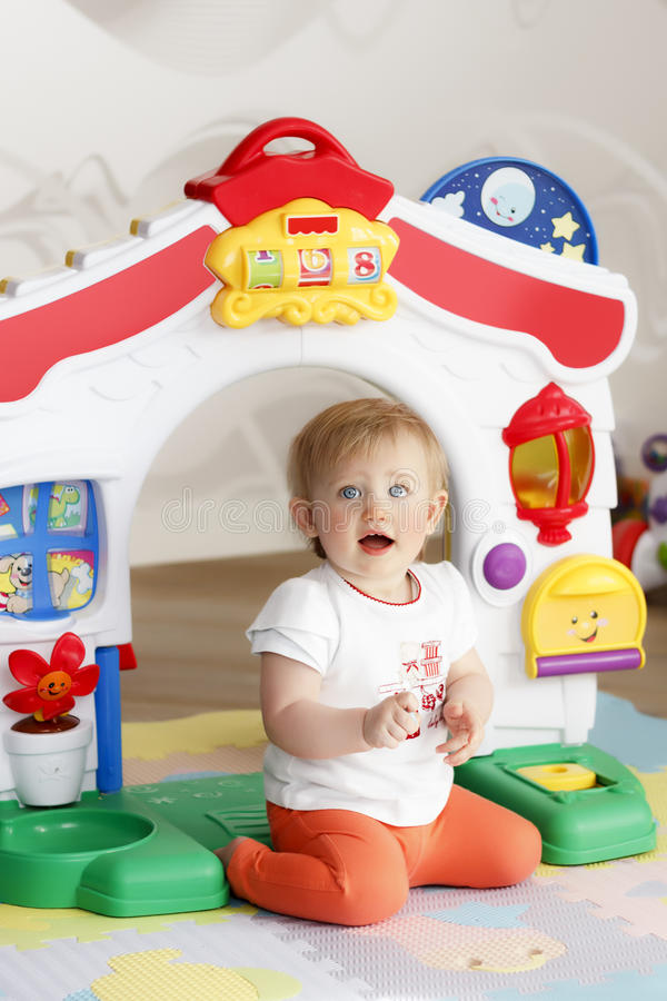 Lilla flickan spelar med en stort leksak och skratta arkivbild