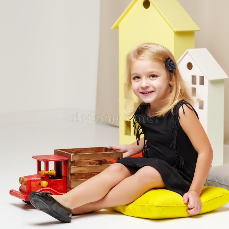Lilla flickan spelar med en träbil royaltyfria bilder