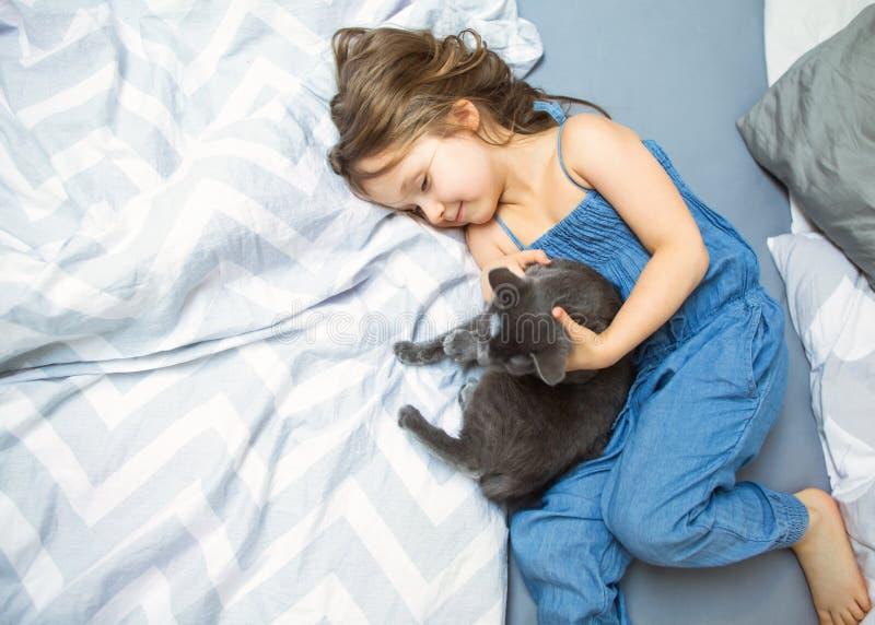 Lilla flickan spelar med hennes katt på sängen royaltyfri foto
