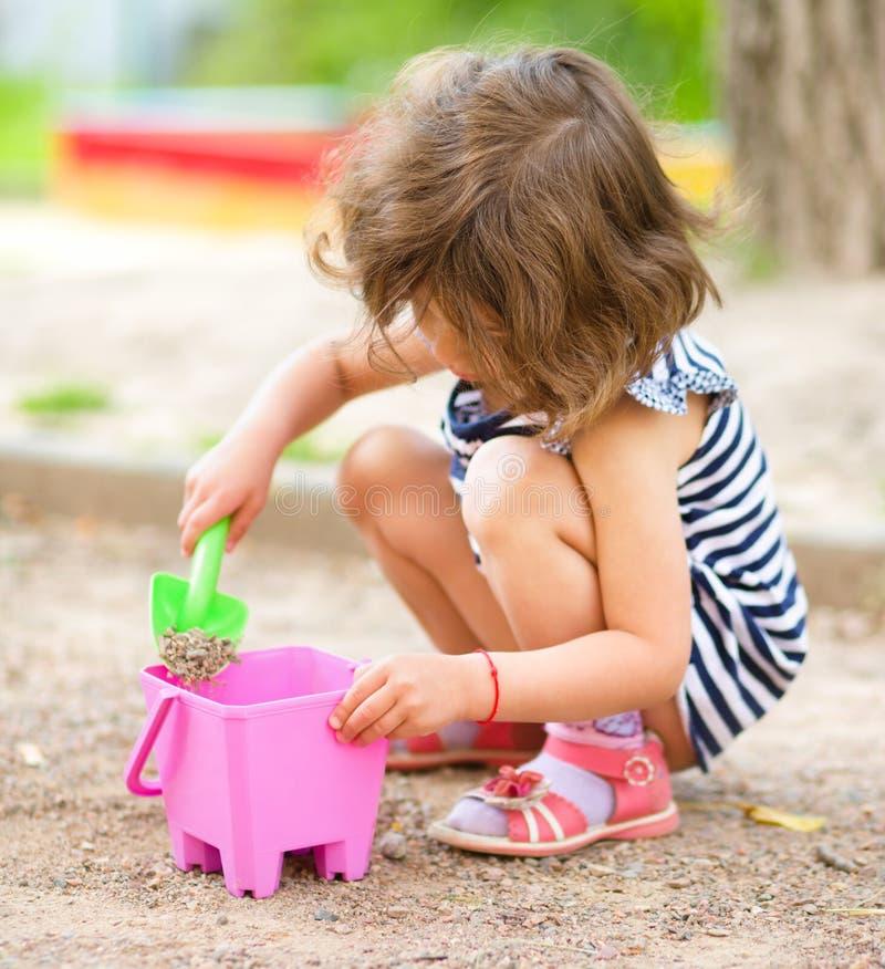 Lilla flickan spelar med sand i lekplats fotografering för bildbyråer