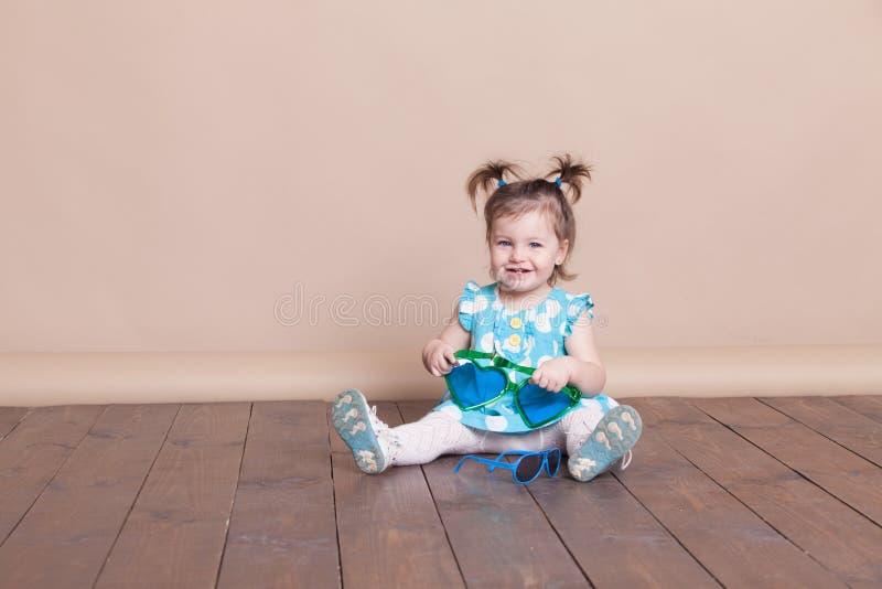 Lilla flickan spelar med stora exponeringsglas, henne som är rolig arkivfoto