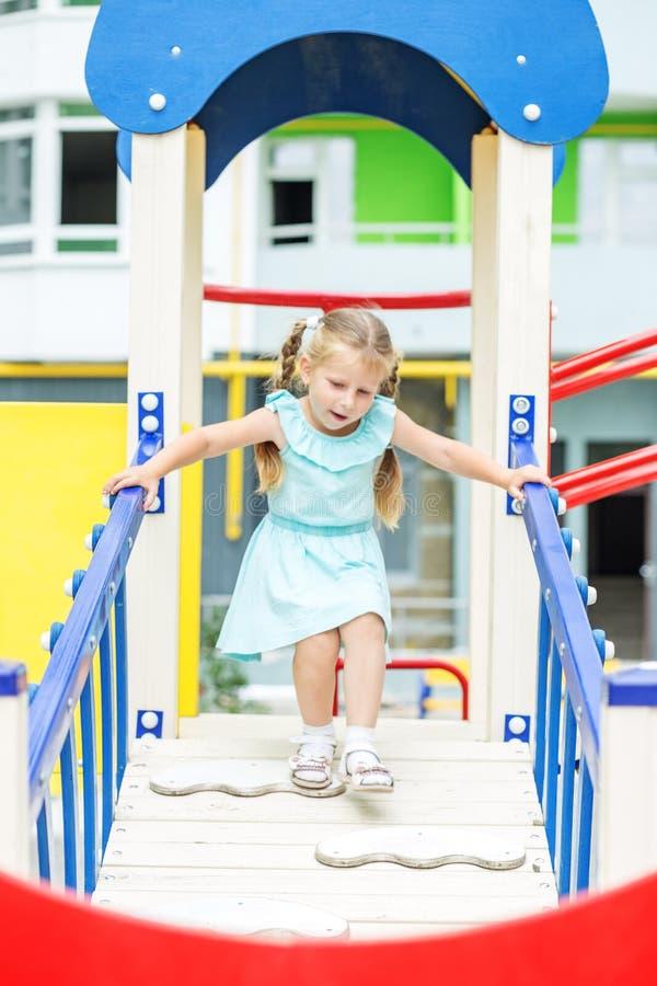 Lilla flickan spelar på lekplatsen Begreppet av barndom, livsstil, uppfostran, dagis arkivbild