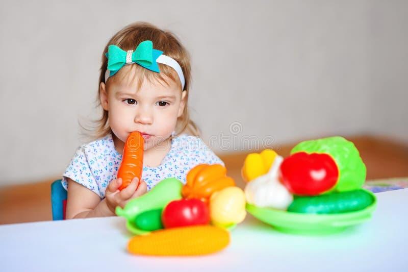 Lilla flickan spelar på tabellen med grönsaker Barnvegetarian Begrepp av sunt äta fotografering för bildbyråer