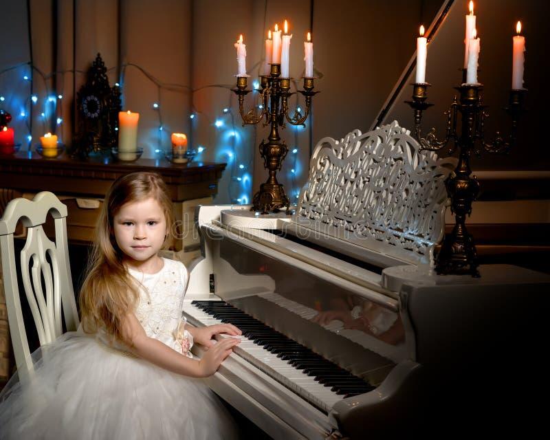 Lilla flickan spelar pianot vid levande ljus arkivbilder