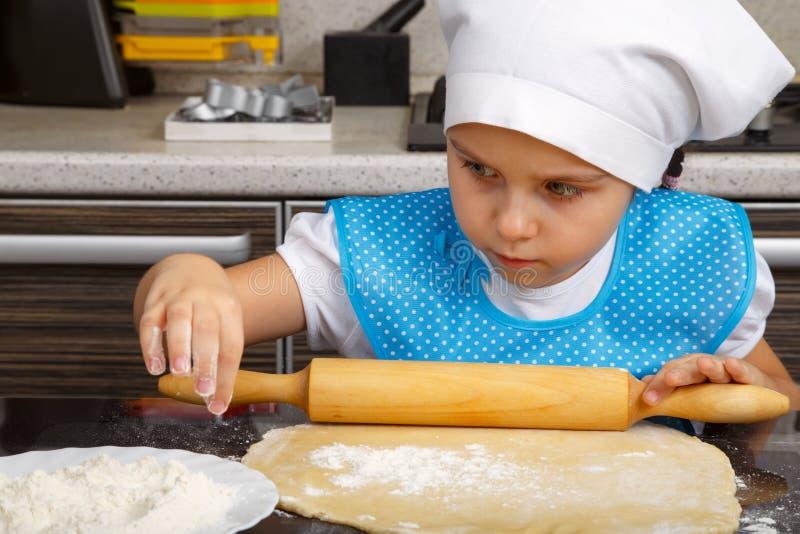 Lilla flickan spelar som en kock royaltyfria foton