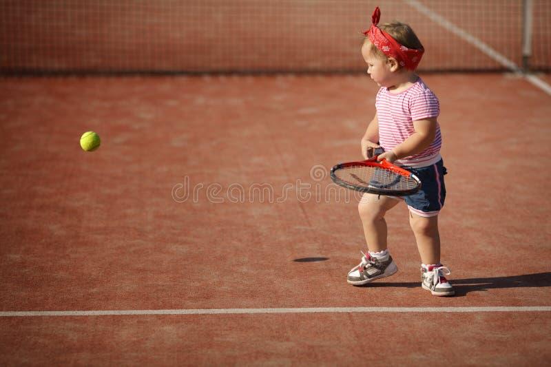 Lilla flickan spelar tennis fotografering för bildbyråer