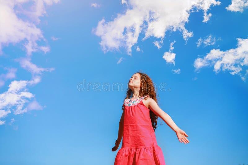 Lilla flickan stängde henne ögon och andas den nya luften royaltyfria foton
