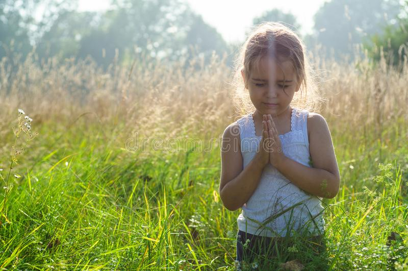 Lilla flickan stängde henne ögon som ber på solnedgången Händer vek i bönbegreppet för tro, andlighet och religion Hopp begrepp royaltyfria bilder