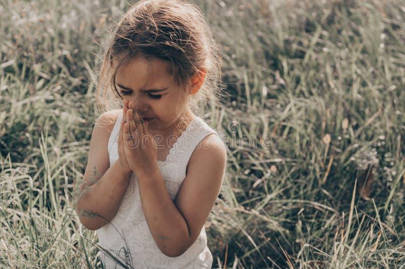 Lilla flickan stängde henne ögon som ber på solnedgången Händer vek i bönbegreppet för tro, andlighet och religion Hopp begrepp arkivbild