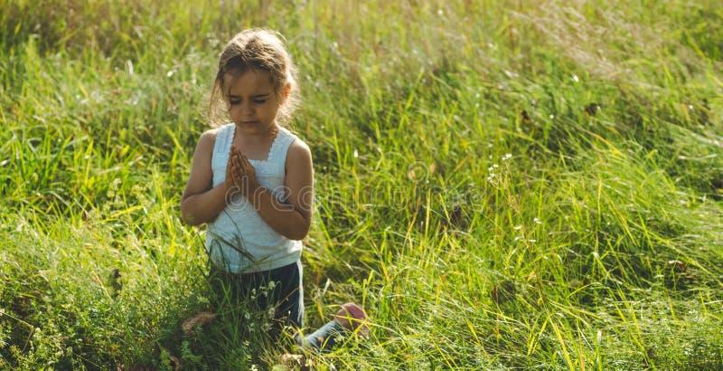 Lilla flickan stängde henne ögon som ber på solnedgången Händer vek i bönbegreppet för tro, andlighet och religion Hopp begrepp arkivfoton