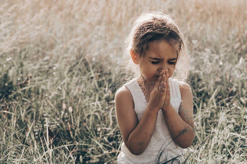 Lilla flickan stängde henne ögon som ber på solnedgången Händer vek i bönbegreppet för tro, andlighet och religion Hopp begrepp royaltyfri bild