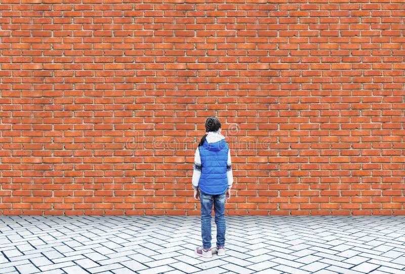 Lilla flickan står i besvär framme av en tegelstenvägg fotografering för bildbyråer