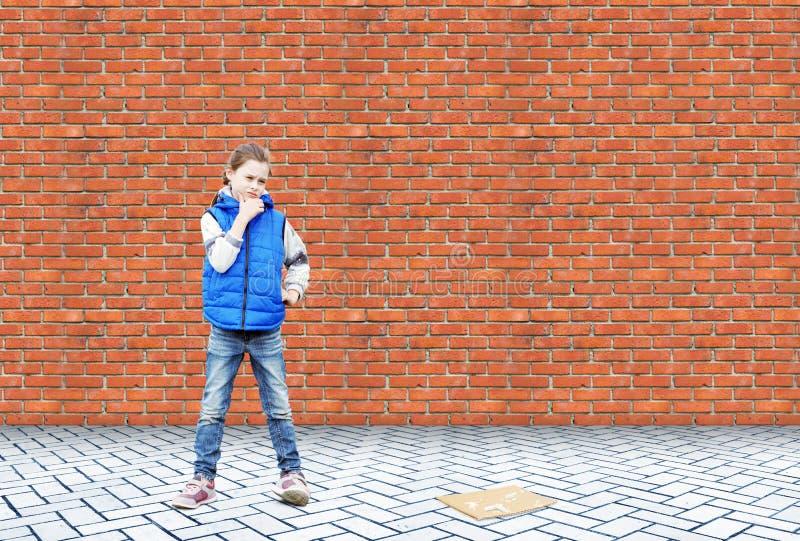 Lilla flickan står i en drömmeri nära en tegelstenvägg royaltyfri fotografi