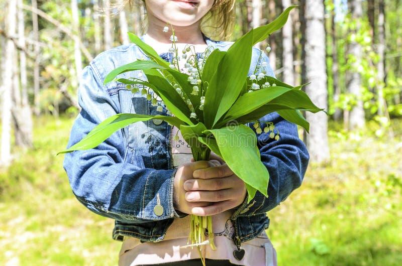 Lilla flickan st?r i en gr?n skog och rymmer en bukett av h?rliga blommaliljekonvaljer arkivfoton