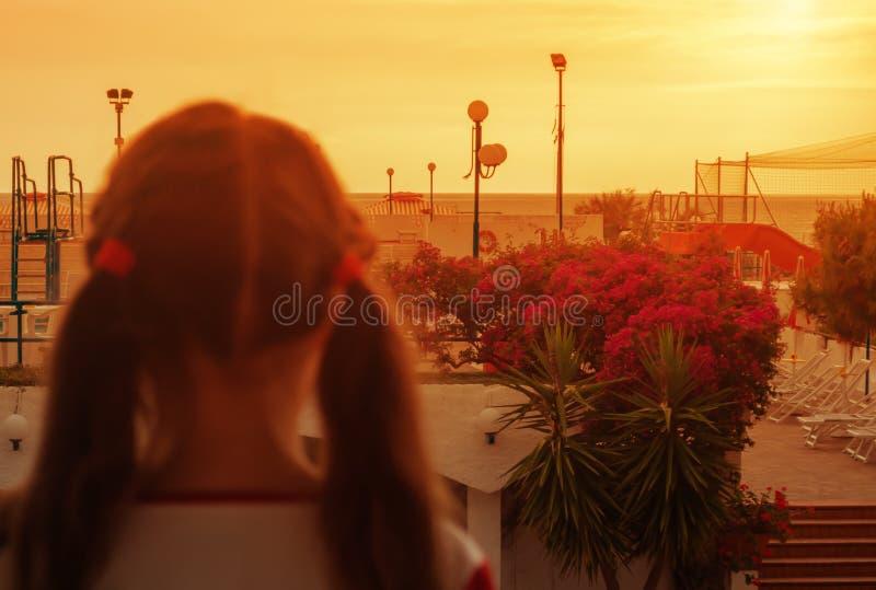 Lilla flickan står på balkongen som ser solnedgången royaltyfri fotografi