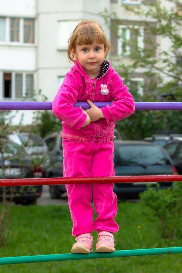 Lilla flickan står på stången och le royaltyfria foton
