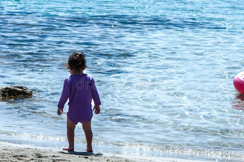Lilla flickan står på stranden royaltyfri foto