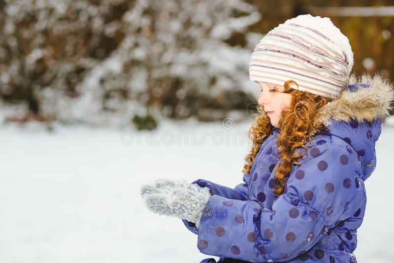 Lilla flickan sträcker hennes hand för att fånga fallande snöflingor Wint arkivfoto