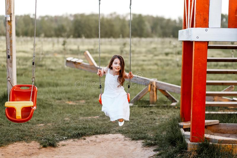 Lilla flickan svänger på en lekplats, när solen skulle ställa in letters den färgrika begreppslyckan för bakgrund white royaltyfria foton