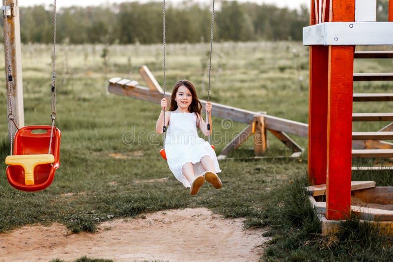 Lilla flickan svänger på en lekplats, när solen skulle ställa in letters den färgrika begreppslyckan för bakgrund white royaltyfri bild