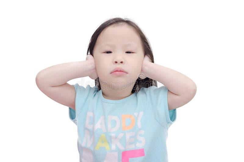 Lilla flickan täcker henne öron vid händer över vit royaltyfri fotografi