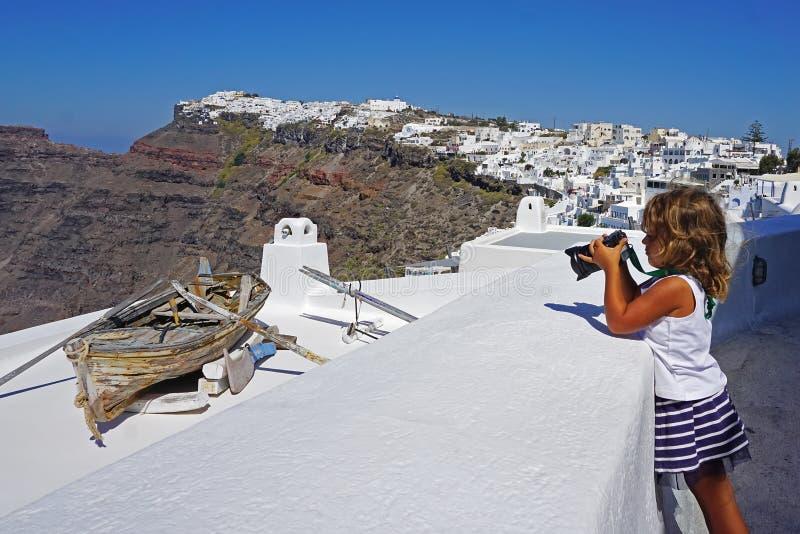 lilla flickan tar bilder av härliga sikter av Santorini royaltyfria bilder