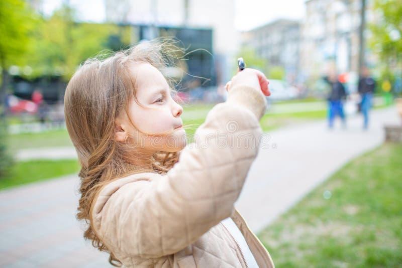 Lilla flickan tar bilder från telefonen arkivfoton