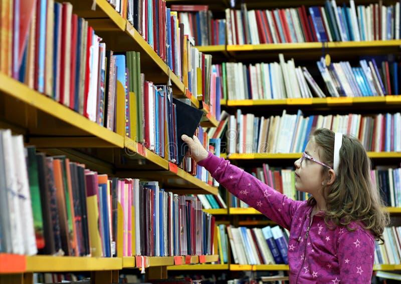 Lilla flickan tar en bok royaltyfria bilder