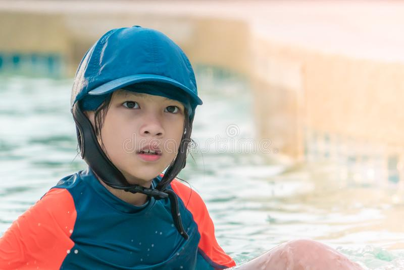 Lilla flickan tröttade mycket, i att simma den utbildande pölen royaltyfria foton