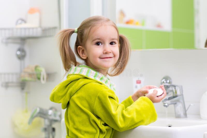 Lilla flickan tvättar hennes händer i badrummet royaltyfri foto