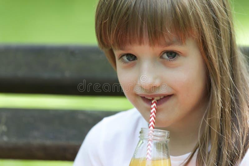 Lilla flickan tycker om en härlig och solig dag och drickafruktsaft royaltyfria foton