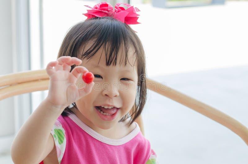 Lilla flickan tycker om till att äta tomaten royaltyfri fotografi