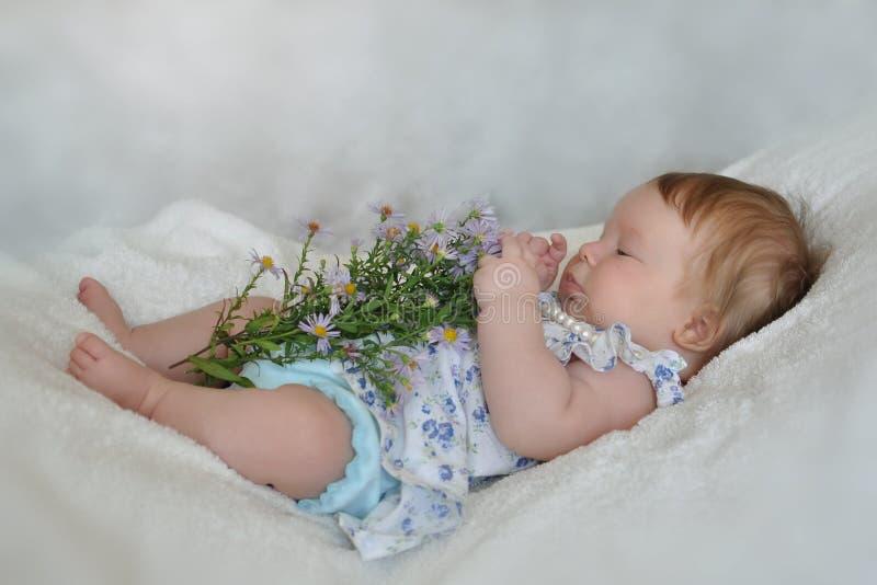 Lilla flickan undersöker blommor arkivbild