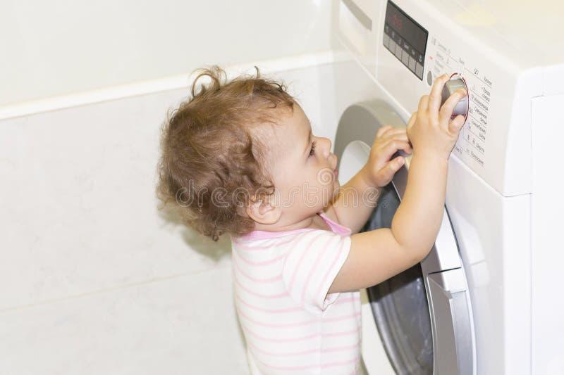 Lilla flickan väljer ett tvättande funktionsläge på en tvättmaskin Årigt Caucasian barn 1 royaltyfri bild