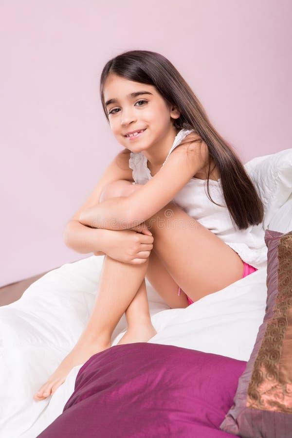Lilla flickan vaknade upp i säng fotografering för bildbyråer