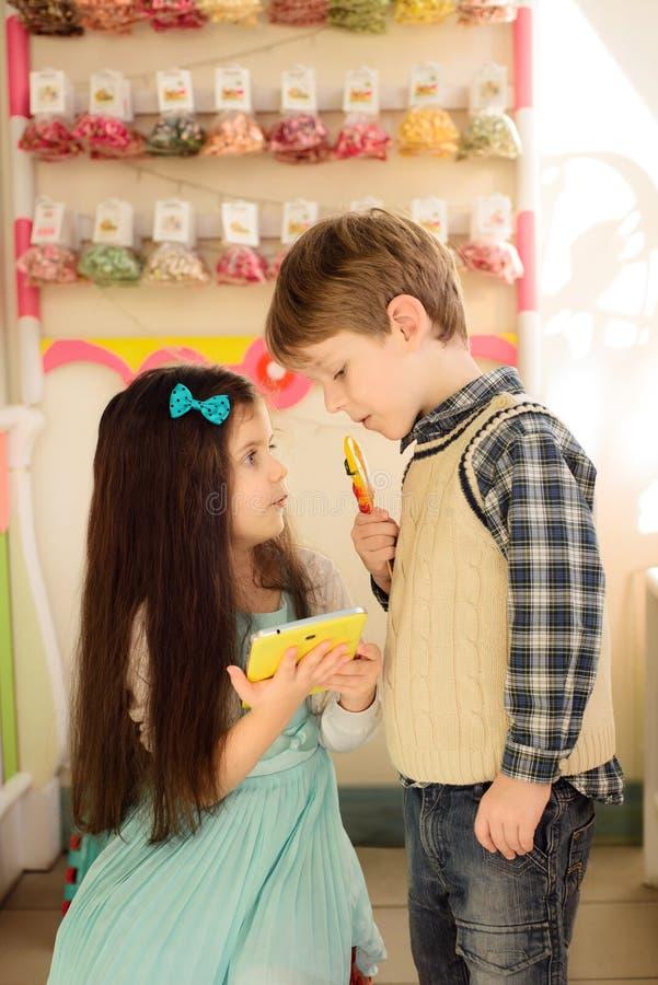 Lilla flickan visar pojken hur man använder minnestavlan royaltyfria foton