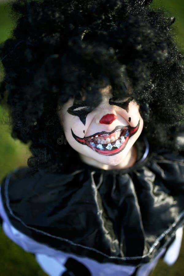 Lilla Kid som tryckts in i Scary Clown Costume för Trick eller för behandling på Halloween fotografering för bildbyråer