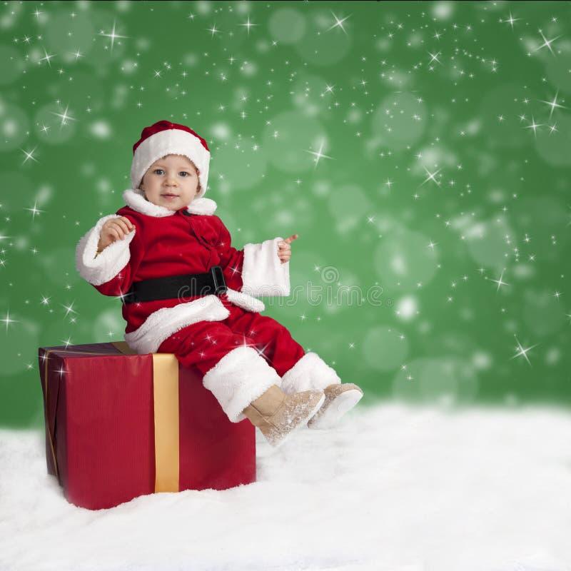 Lilla Santa Claus som placeras på en julklapp i snön arkivbilder