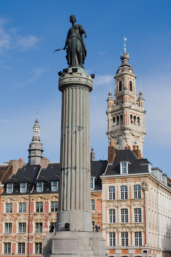 Lille, France. Belfry, historical houses and the statue and column of Deesse (1845), the goddess and a symbol of the city. The statue commemorates the siege of royalty free stock photo
