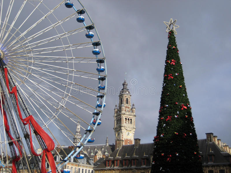 Lille, France at Christmas. Christmas tree and ferris wheel in the famous christmas market in Lille, France. With Chamber of Commerce building in the background stock images