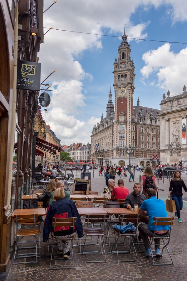 Belfry of the Chambre de Commerce in Lille, FR. Lille, France - 15 June 2018: People walking On Pierre Mauroy street. Belfry of the Chambre de Commerce in the royalty free stock photo