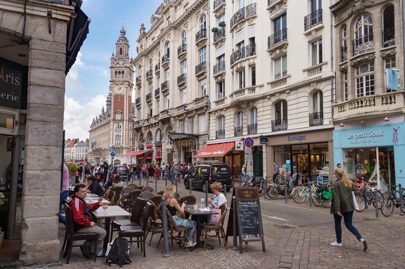 Belfry of the Chambre de Commerce in Lille, FR. Lille, France - 15 June 2018: People walking On Pierre Mauroy street. Belfry of the Chambre de Commerce in the stock photo