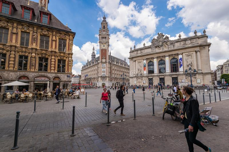 Belfry of the Chambre de Commerce and Opera House in Lille, FR. Lille, France - 15 June 2018: People walking in the Theatre Square. Belfry of the Chambre de royalty free stock images