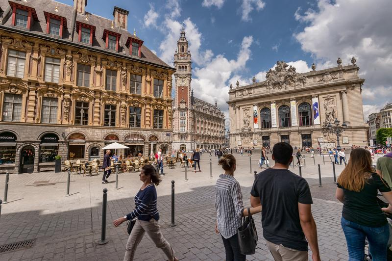 Belfry of the Chambre de Commerce and Opera House in Lille, FR. Lille, France - 15 June 2018: People walking in the Theatre Square. Belfry of the Chambre de stock photo