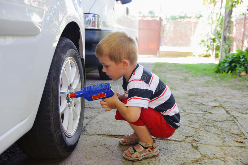 Lillte child playing in auto mechanic royalty free stock image