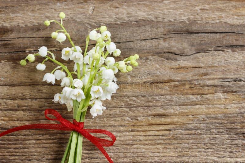 Lilly av dalen blommar på träbakgrund. fotografering för bildbyråer
