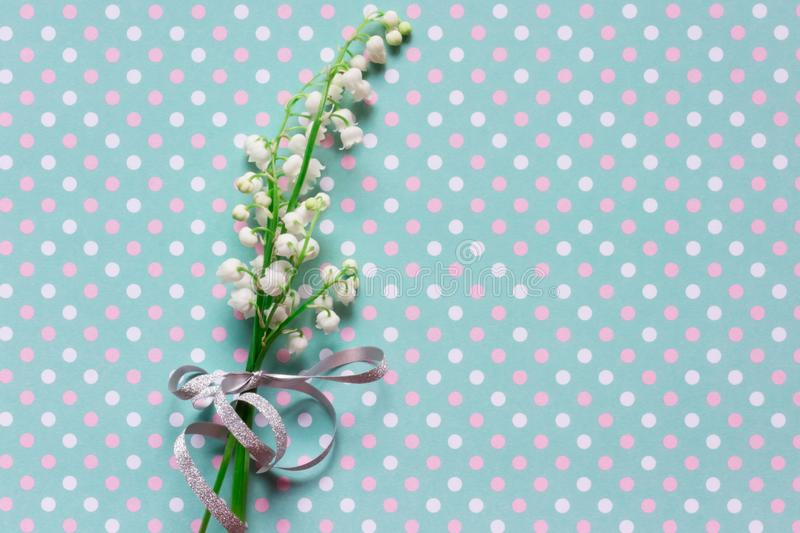Lilly of valley on dotted pattern background. Lilly of valley on white pink and blue dotted pattern background royalty free stock image