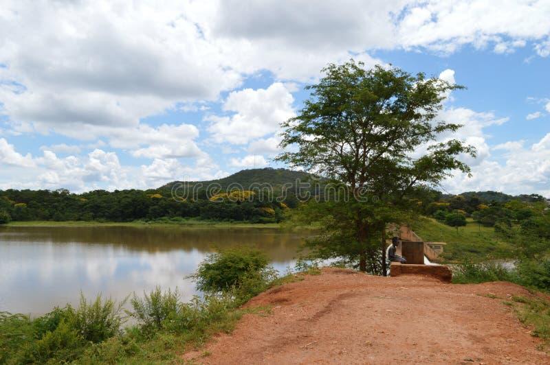 LILONGWE, MALAWI, AFRYKA - 1 KWIETNIA 2018 R.: Dwóch afrykańskich chłopców siedzi pod drzewem koło zapory Kamuzu fotografia stock